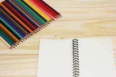 Тетрадь и покрашенные карандаши Стоковые Изображения