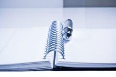 Тетрадь и ручка дела на таблице в офисе Стоковые Изображения