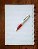 Тетрадь и ручка на деревянной предпосылке Стоковые Фотографии RF