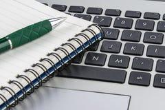 Тетрадь и ручка на клавиатуре компьтер-книжки, конец вверх Стоковая Фотография RF