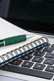 Тетрадь и ручка на клавиатуре компьтер-книжки, конец вверх Стоковое Фото