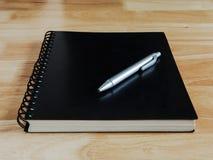 Тетрадь и ручка на деревянном столе Стоковая Фотография RF