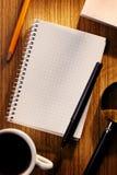 Тетрадь и чашка кофе решетки на столе Стоковые Изображения