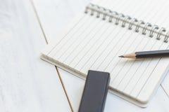 Тетрадь, карандаш и ластик на деревянном столе, взгляде конца-вверх, концепции рабочего места, канцелярские товаров, backgr Стоковое Фото