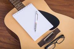 Тетрадь, карандаш и eyeglasses гитары Стоковые Фото