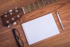 Тетрадь, карандаш и eyeglasses гитары Стоковая Фотография RF