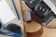 Тетрадь, карандаш, солнечные очки, и камера на деревянном поле Стоковая Фотография