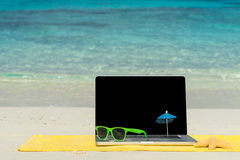 Тетрадь компьютера на пляже - предпосылке деловых поездок Стоковое Изображение RF