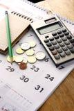 Тетрадь, монетки, календарь, калькулятор и карандаш на таблице Стоковое фото RF
