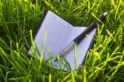 Тетрадь на траве стоковые фотографии rf