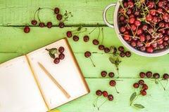 Тетрадь на яркой деревянной предпосылке с ягодами вишни Стоковые Фото