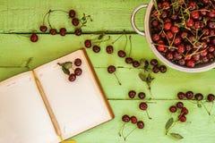 Тетрадь на яркой деревянной предпосылке с ягодами вишни Стоковое Изображение
