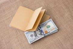 Тетрадь помещенная около банкнот доллара США Стоковые Изображения