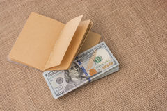 Тетрадь помещенная около банкнот доллара США Стоковое фото RF