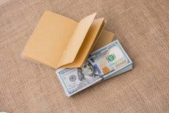 Тетрадь помещенная около банкнот доллара США Стоковые Фото