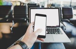 Тетрадь пользы молодого человека или портативный компьютер и телефон в авиапорте Стоковые Изображения