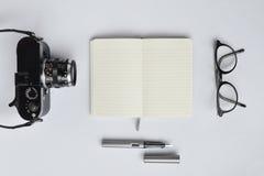 Тетрадь, ручка, и камера, на белой предпосылке стоковое фото rf