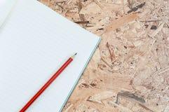 Тетрадь с изолятом карандаша на деревянной предпосылке Стоковое Изображение