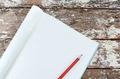 Тетрадь с изолятом карандаша на деревянной ретро предпосылке Стоковое фото RF