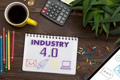 Тетрадь с ИНДУСТРИЕЙ 4 примечаний 0 на таблице офиса с инструментом Стоковые Изображения