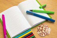 Тетрадь с карандашами и ручками на таблице стоковые изображения rf