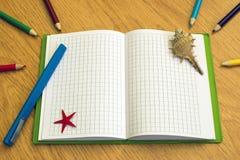 Тетрадь с карандашами и ручками на таблице стоковая фотография rf