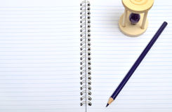 Тетрадь с карандашем и стеклом времени Стоковая Фотография