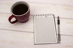 Тетрадь с кофе на деревянном столе Стоковое Изображение RF