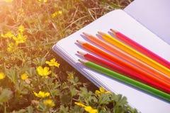 Тетрадь с покрашенными карандашами Стоковые Изображения RF