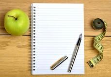 Тетрадь с плодоовощ и сантиметром яблока Стоковые Фотографии RF