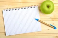 Тетрадь с плодоовощ ручки и яблока Стоковая Фотография