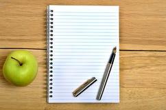 Тетрадь с плодоовощ ручки и яблока Стоковое Фото