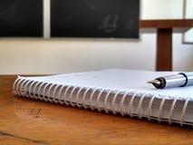 Тетрадь с ручкой в аудитории Стоковое Изображение RF