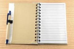 Тетрадь с ручкой на деревянном поле Стоковое фото RF
