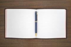 Тетрадь с ручкой на таблице Стоковое Фото