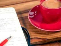 Тетрадь с чашкой эспрессо стоковые изображения