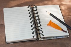 Тетрадь с черным карандашем, свежим цветком orage на деревянном столе Стоковые Изображения