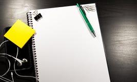 Тетрадь с чистым листом бумаги, красит липкие примечания, ручку, smartphone и зажимы на деревянном столе Стоковая Фотография RF