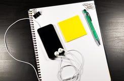 Тетрадь с чистым листом бумаги, красит липкие примечания, ручку, smartphone и зажимы на деревянном столе Стоковое Изображение RF