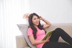 Тетрадь чтения женщины сидя на кресле Стоковые Изображения RF