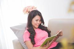 Тетрадь чтения женщины сидя на кресле Стоковое Изображение RF