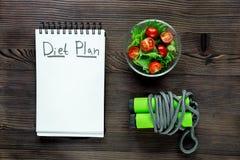 Тетрадь для плана диеты, салат с свежими продуктами и веревочка скачки на насмешке взгляд сверху деревянного стола вверх Стоковые Изображения RF