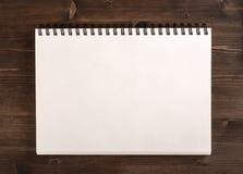 Тетрадь для эскизов на деревянной предпосылке Стоковая Фотография