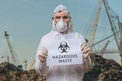 Техник в coverall в месте захоронения отходов предупреждает против опасных токсичных отходов Стоковые Фотографии RF