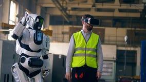 Техник в VR-стеклах и робот повторяя его движения сток-видео