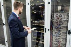 Техник держа доску сзажимом для бумаги пока анализирующ сервера Стоковые Фотографии RF