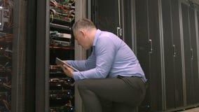 Техник используя ПК таблетки пока анализирующ сервера видеоматериал