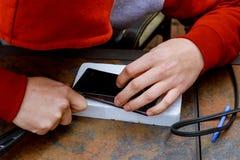 Техник исправляющ и заменяющ сломленный экран на умном телефоне Стоковые Изображения RF