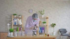 Техник лаборатории женщины проводит исследование используя микроскоп сток-видео