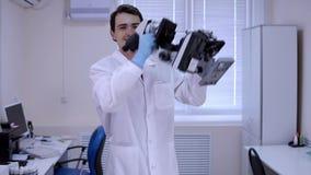 Техник лаборатории молодого человека танцует в лаборатории с микроскопами в руках видеоматериал